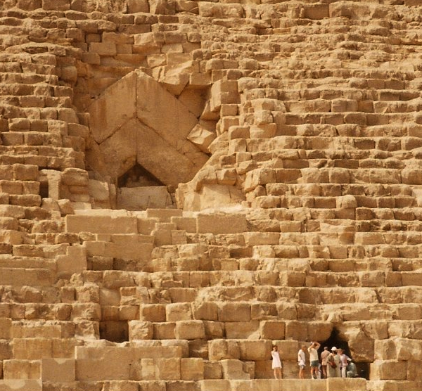 The entrance to Khufu's Pyramid, with the Thieves' Entrance in the lower right corner. The people entering the Thieves' Entrance give an indication of the size of the blocks involved. Note the large blocks and beams of the Main Entrance—there are larger blocks deeper within and much higher up. (Photo by Keith Payne)