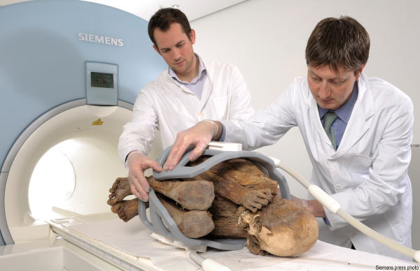 Dr. Frank Ruhli of the Swiss Mummy Project (right) prepares a mummy for a CT scan.  In this case it is a 1,000-year-old mummy from Peru (center), but the process is the same (Photo courtesy of Siemens AG)