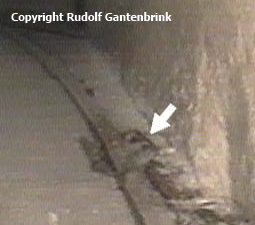 Rudolf Gantenbrink's robot crawler, Upuaut-2, took this shot of an object in QCN that might correspond to the riveted hook recovered by Dixon. The track-like object is an iron rod abandoned by previous explorers (Photo by Rudolf Gantenbrink)