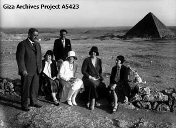 Visit of Queen Marie of Romania, Harvard Camp, looking southeast towards the Menkaure Pyramid; from left to right: George Reisner, Mrs. Mary Reisner, Hansmartin Handrick (standing behind), Queen Marie's youngest daughter Princess Ileana (white dress), Queen Marie (dark dress), and Miss Mary Reisner; March 17, 1930 (Giza Archives Project A5423)