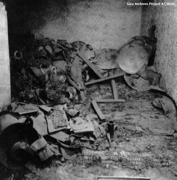 From this view of the tomb the disintegrated bed can be barely discerned amid the rubble.  The regular inlays of the footboard can be seen in the lower right of the picture, but otherwise the positions of the metal fittings had to be noted to determine where the wooden elements would have fitted together (Giza Archives Project A 3824).