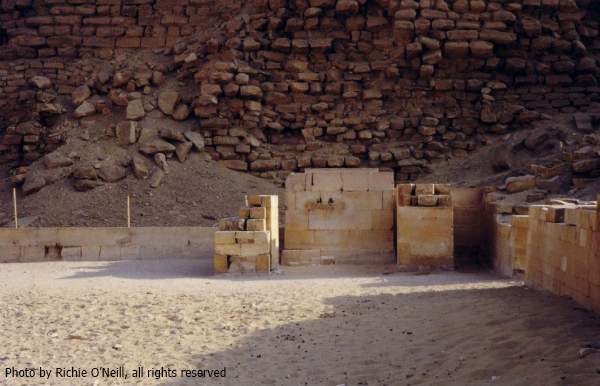 "The serdab court at the Step Pyramid.  The ""peek holes"" can be seen in the serdab.  Within is a replica of the statue of Djoser, the original is in the Egyptian Museum in Cairo (Photo by Richie O'Neill)"