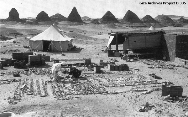 Workmen sorting royal shabti figures at Nuri, Sudan, with the pyramids in the background, March 19, 1917 (Giza Archives Project D 335)