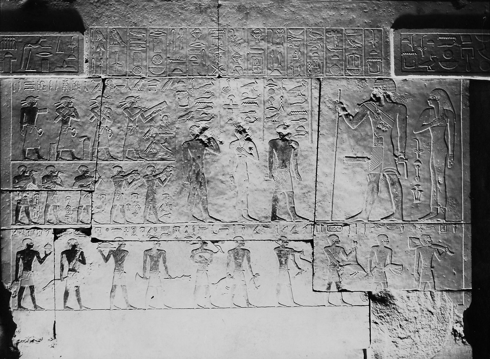 "Kaninuset I Blocks of relief from G 2155, Kaninisut [I], chapel, western wall (relief between false doors depicting standing figures of Kaninisut and his wife Neferhanisut and their three children, Harwer, Wadjethetep, and Kaninisut ""the younger""; registers of scribes and ka-priest: [top register] Wehemka, Kaemwehem, Mesy, Tjenti, [middle register] Penu, Wahib, Itjef, Khufuseneb, Ity; and register of offering bearers below: [bottom register] Niankhhathor, Kairi, Mernetjerukhufu, Seshmu, Seneb, Iinefret, Shendju, Khufuankh, Mer[...]khufu, Senebdisu). Currently in the Kunsthistorisches Museum, Vienna (ÄS 8006). Photo ID KHM_o_neg_nr_0159, photo and description courtesy of the Giza Archives maintained by Harvard University and the Museum of Fine Arts Boston, online at Digital Giza."