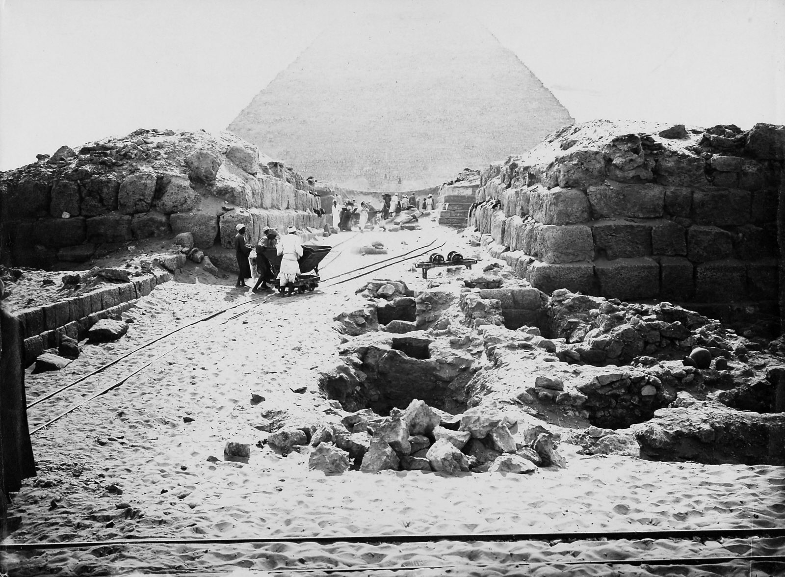 D 116 and mastaba of Nu(?) (foreground right), D 117 (foreground left), looking south along street (III) between G 4360 (= III n, to west) and G 4460 (= IV n, to east). Photo ID KHM_o_neg_nr_0539, photo and description courtesy of the Giza Archives maintained by Harvard University and the Museum of Fine Arts Boston, online at Digital Giza.