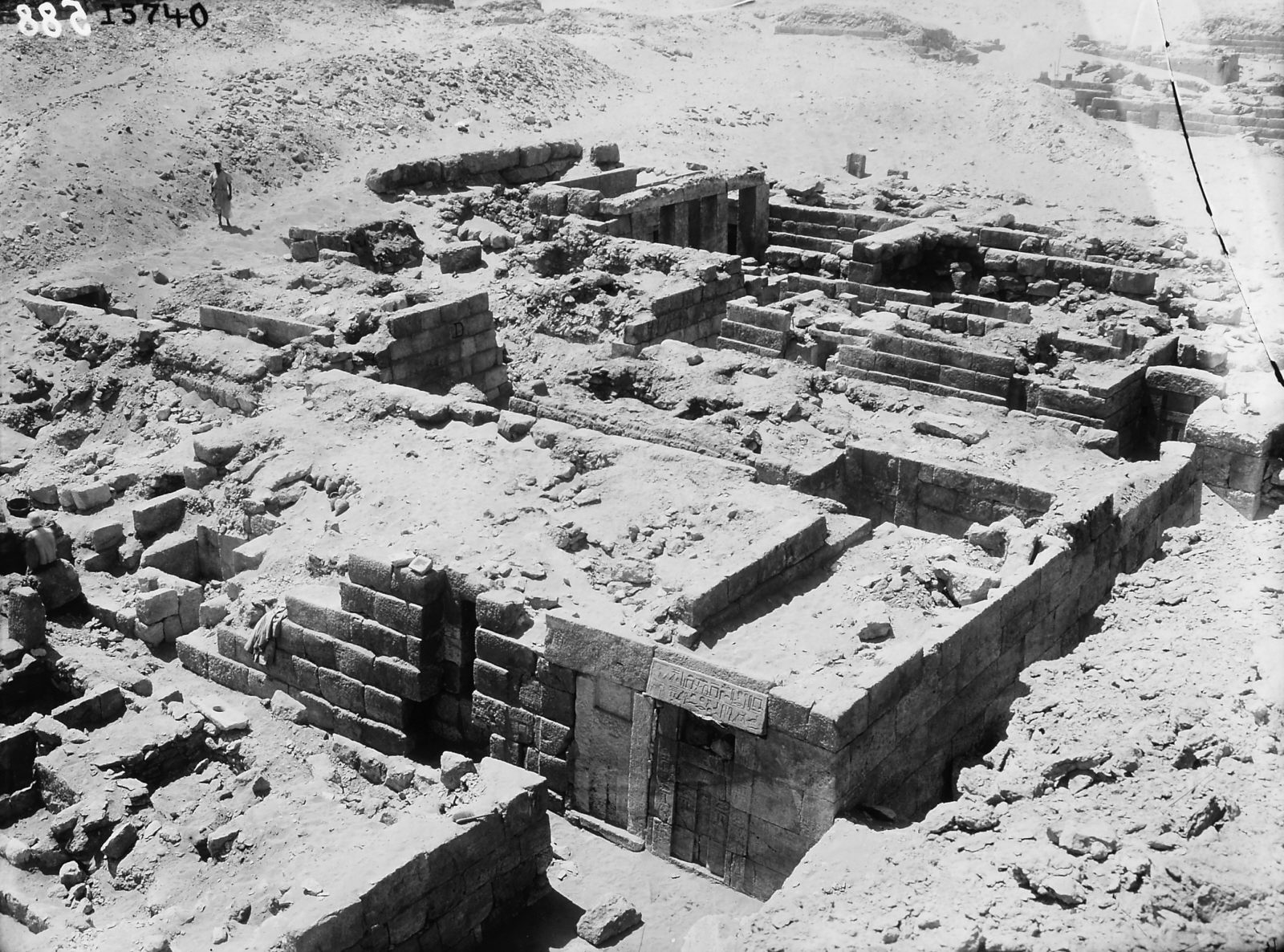 D 201, with false doors on W wall of corridor chapel (foreground), D 202, D 203, and D 204 (sequentially to W), D 208, with pillared portico (partially excavated, background center), looking SW. Photo ID KHM_AEOS_I_5740, photo and description courtesy of the Giza Archives maintained by Harvard University and the Museum of Fine Arts Boston, online at Digital Giza.