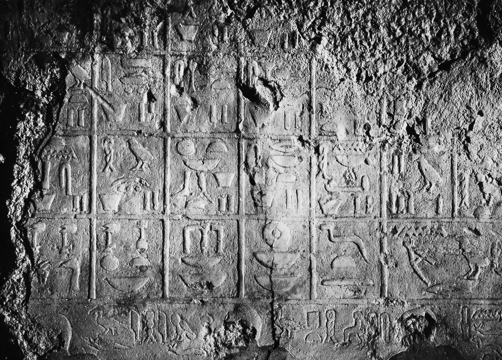 Mastaba of Meruka (2), chapel, western wall (middle), inscription (compartment offering list, immediately above bottom register of offering bearers carrying forelegs; heads of two of Meruka's sons, Ihiemsaf and Ptahshepses, visible), looking west. Photo ID KHM_AEOS_II_2715, photo and description courtesy of the Giza Archives maintained by Harvard University and the Museum of Fine Arts Boston, online at Digital Giza.