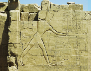 Aggrandizing the pharaoh and demonstrating his dominion over all other lands were vital and eternal functions of both art and writing. The typical image, going back to Narmer's time, was of the pharaoh smiting his enemies, as Thutmose III is doing here on the wall of the seventh pylon at the Temple of Amun, Karnak.